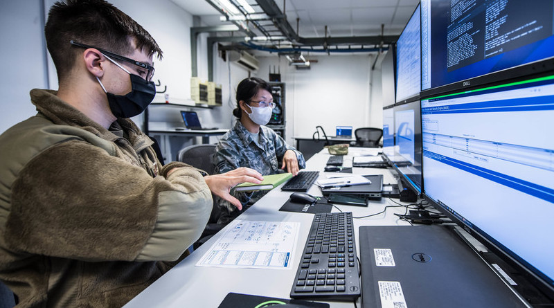 Air Force Senior Airman Rose Li, right, hands a notebook to Air Force Airman 1st Class Eric Gardella while monitoring malicious network activity during exercise Tacet Venari at Ramstein Air Base, Germany, July 2, 2020. Both are cyber readiness technicians with the 86th Communications Squadron. Photo Credit: Air Force Staff Sgt. Devin Boyer