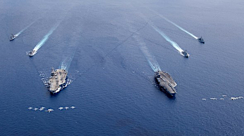 Planes from Carrier Wing 5 and Carrier Wing 17 fly in formation as the aircraft carriers USS Nimitz and USS Ronald Reagan, and other ships sail together in the South China Sea, July 6, 2020. Courtesy U.S. Navy