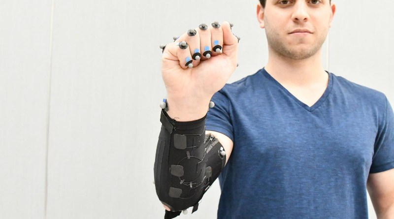 Moritz Graule, a graduate student at SEAS, demonstrates a fabric arm sleeve with embedded sensors. The sensors detect the small changes in the Graule's forearm muscle through the fabric. Such a sleeve could be used in everything from virtual reality simulations and sportswear to clinical diagnostics for neurodegenerative diseases like Parkinson's Disease. CREDIT: (Image courtesy of Oluwaseun Araromi/Harvard SEAS)