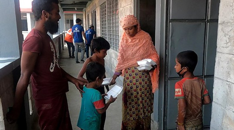 A Rohingya refugee distributes food packages to her children in front of their new home in Bhashan Char, Bangladesh, Dec. 5, 2020. Photo Credit: BenarNews