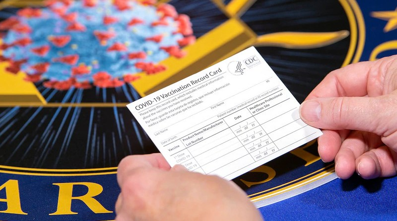 A Department of Health and Human Services employee holds a COVID-19 vaccine record card. Photo Credit: EJ Hersom, DOD