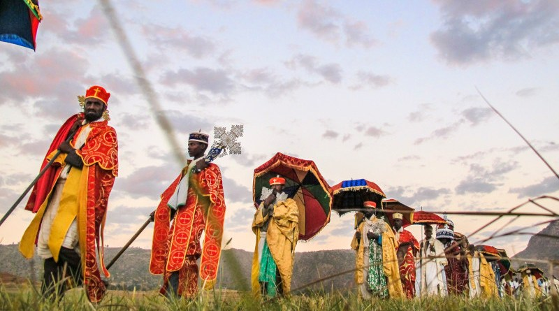 Village elders lead the Timket procession across the village. They walk through their green fields that are flourishing because of their agricultural rehabilitation efforts. Tigray, Ethiopia, 2014. Photo Credit: Nava Derakhshani