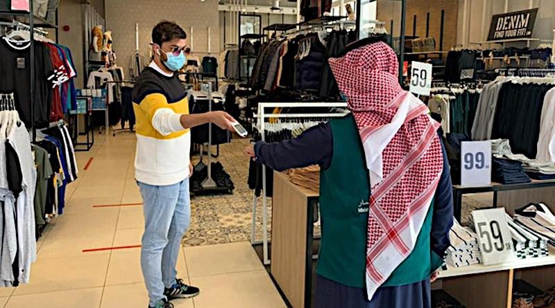 Retailer in Saudi Arabia checking health status via the Tawakkalna app of client. Photo Credit: SPA