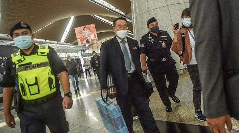 North Korean diplomat Kim Yu Song is escorted by Malaysian police at Kuala Lumpur International Airport, March 21, 2021. [S Mahfuz/BenarNews]