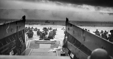 """WWII: Europe: France; """"Into the Jaws of Death — U.S. Troops wading through water and Nazi gunfire"""", circa 1944-06-06. D-Day. Photo Credit: Chief Photographer's Mate (CPHoM) Robert F. Sargent, Wikipedia Commons"""