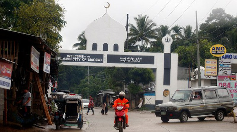 A motorcyclist passes an arch marking the limits of Marawi City in the southern Philippines. Photo Credit: Jeoffrey Maitem / BenarNews