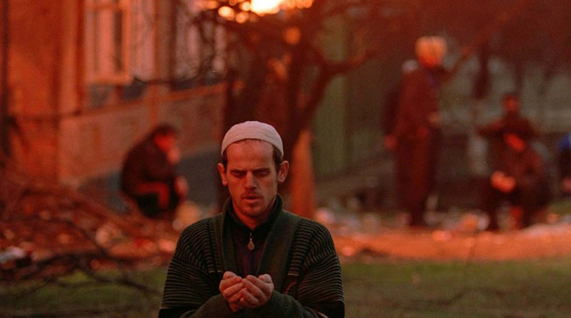 A Chechen man prays during the Battle of Grozny. Photo Credit: Mikhail Evstafiev, Wikipedia Commons