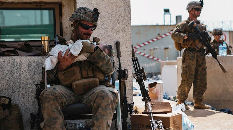 A Marine calms an infant at Hamid Karzai International Airport, Kabul, Afghanistan, Aug. 20. Service members and coalition partners are assisting the Department of State with a non-combatant evacuation operation in Afghanistan. Photo Credit: Marine Corps Sgt. Isaiah Campbell
