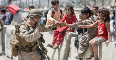 A USMC Marine with Special Purpose Marine Air-Ground Task Force-Crisis Response-Central Command plays with children at Hamid Karzai International Airport in Kabul, Afghanistan. Photo Credit: DOD/Twitter
