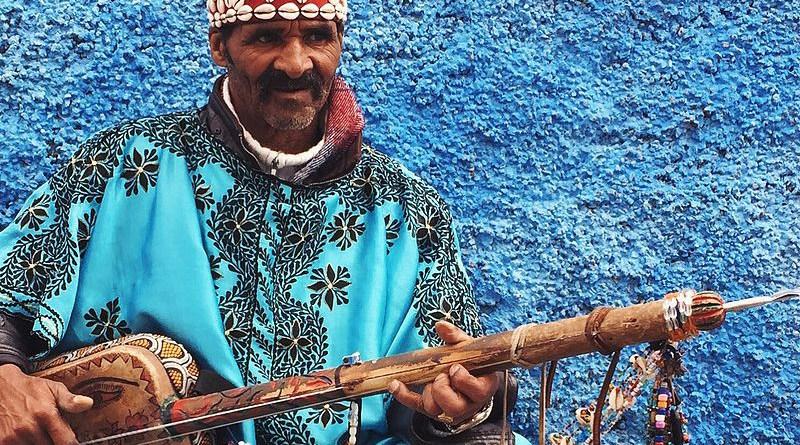 A gnawa performer dressed in traditional gnawa clothing in the Qasbat al-Widaya neighborhood of Rabat, Morocco. Photo Credit: Sambasoccer27, Wikipedia Commons