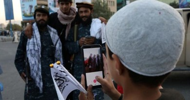 A young boy takes a photo of members of Taliban in Afghanistan. Photo Credit: Fars News Agency