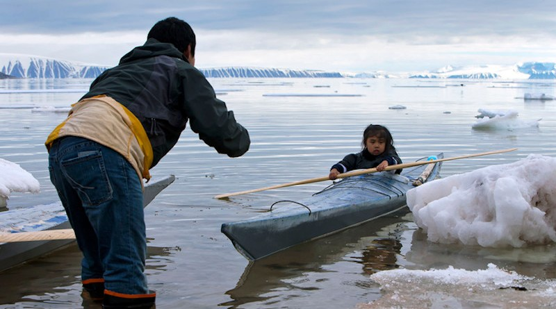 In the photo, Qillaq Danieldsen is teaching a child to paddle near Siorapaluk in northwest Greenland. CREDIT: Carsten Evevang.