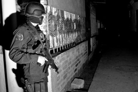 A Special Forces officer of the Grupo Reacion Policial guards an alley during a raid against gang members in El Salvador.