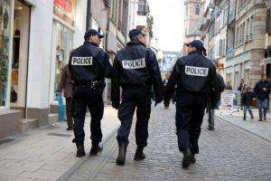 photographie de trois policiers patrouillant dans une rue, de dos