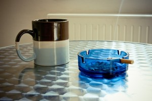 Photographie d'une cigarette qui fume dans un cendrier à côté d'un mug