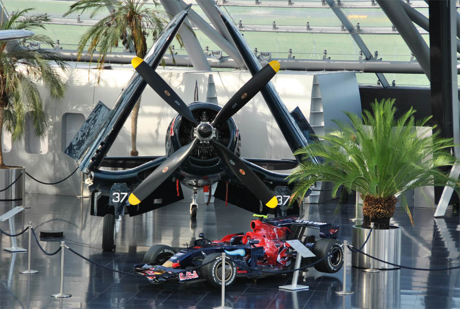 Hangar 7   Red Bull museum   Austria   euro t guide   What to see   6 A Red Bull World War II Vaught F4U 4 Corsair fighter and a Toro Rosso  Formula 1 cars displayed at Hangar 7   Salzburg Airport   as a part of the  Red Bull
