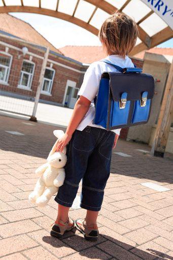 Un niño de espaldas a la puerta del colegio con una mochila y un conejo de peluche ©BELGA/BELPRESS/Turpin Philippe