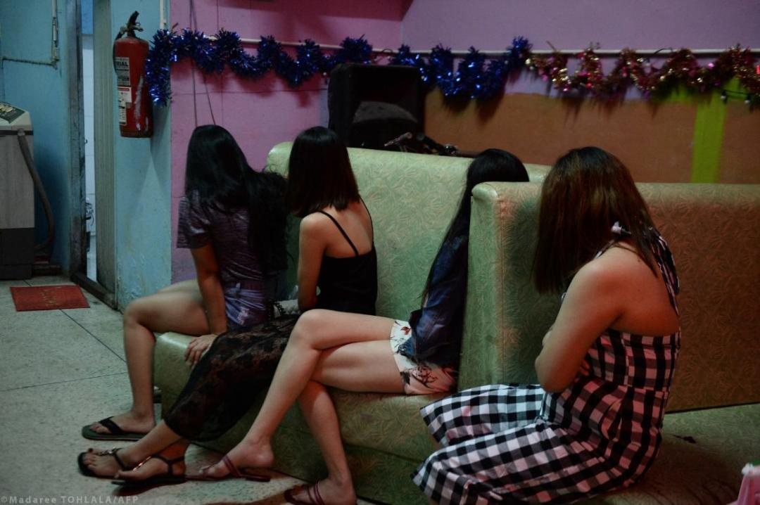 Foreign women are seen sitting inside a bar during a police raid as part of a campaign against prostitution and human trafficking involving women and minors. © Madaree TOHLALA/AFP