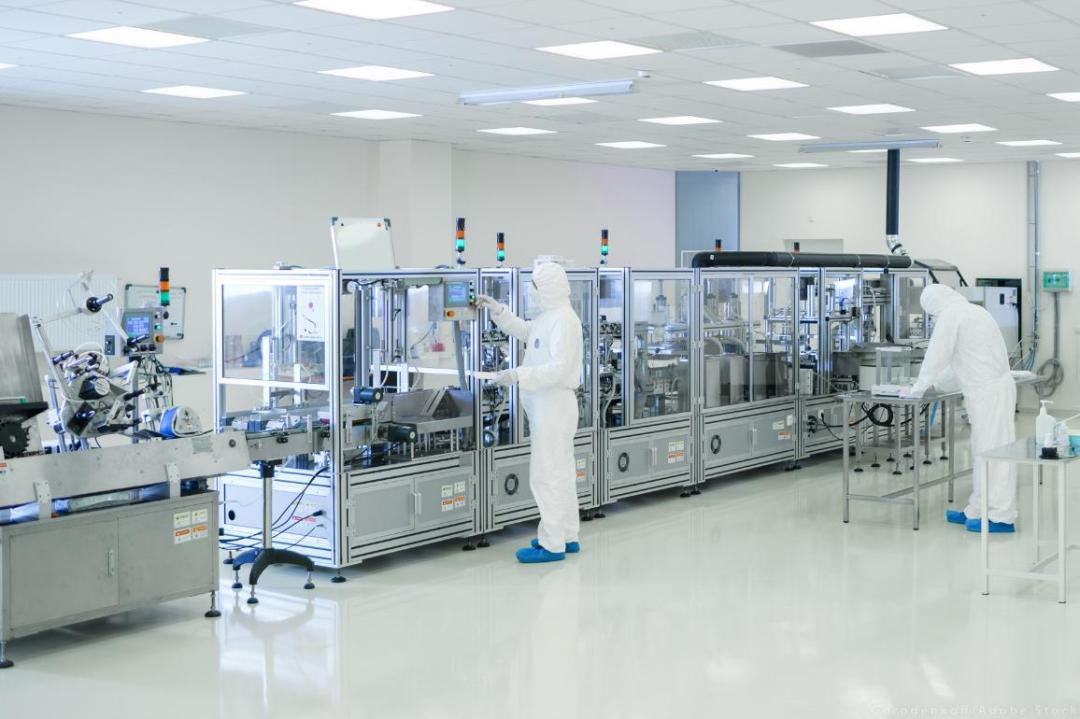 Shot Of Sterile High Precision Manufacturing Laboratory where Scientists in Protective Coverall's Use Computers and Microscopes, doing Pharmaceutics, Biotechnology and Semiconductor Research. ©AdobeStock/Gorodenkoff