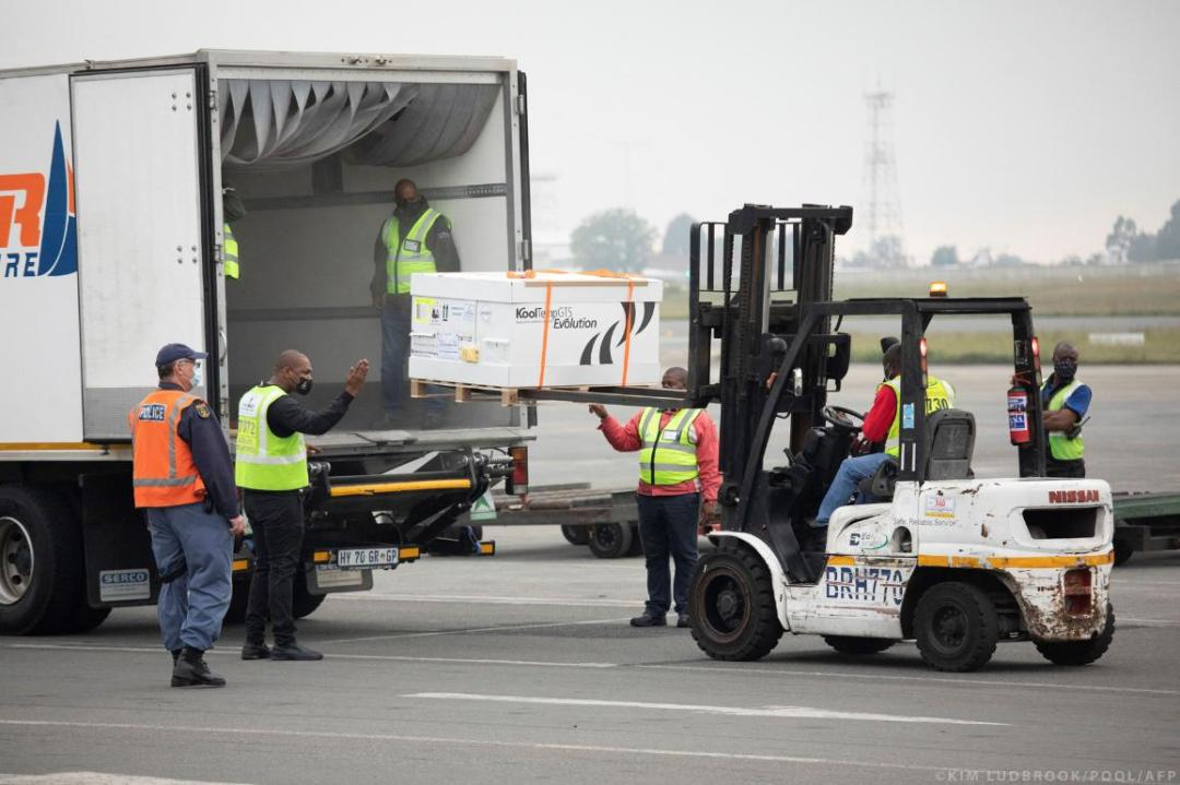 Workers transport the second shipment of the Johnson & Johnson Covid-19 coronavirus vaccine upon its arrival at the O R Tambo International Airport in Johannesburg on February 27, 2021. © Kim LUDBROOK/POOL/AFP