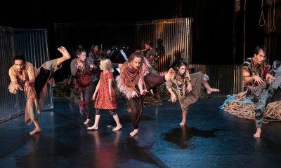 Viele Kinder und Erwachsene auf einer Bühne, ohne erkennbare, gemeinsame Choreografie, aber tanzend