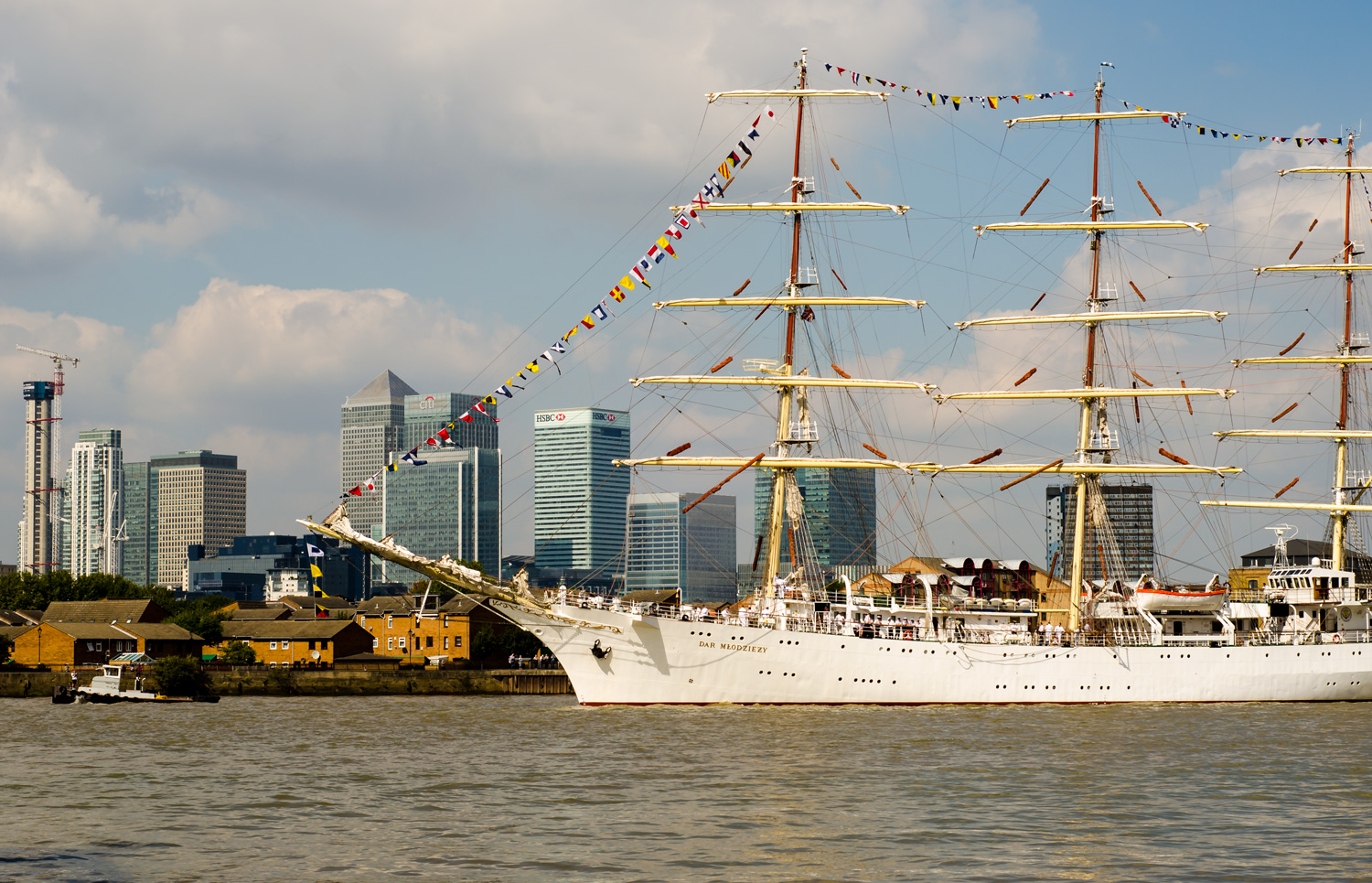 The Polish built Dar Mlodziezy sailing down the Thames and passing by Canary Wharf in London