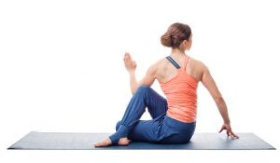 Beautiful sporty fit yogini woman practices yoga asana ardha matsyendrasana - half spinal twist pose isolated on white background