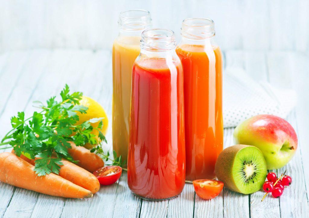 Três garrafas de sucos detox feitos com frutas e legumes. As garrafas estão dispostas sobre uma mesa de madeir branca. Cenouras, maça, kiwi, laranja e salsinha decoram a mesa.