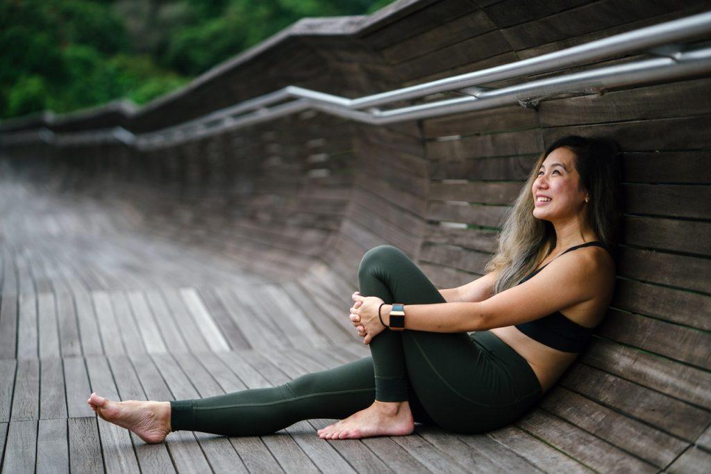 Mulher vestindo roupa de ginástica sentada em um caminho de madeira que se estende até o corrimão. Ela sorri e segura seu joelho direito.
