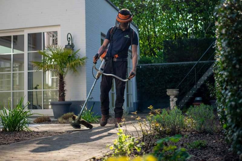 Mann mit einem Rasentrimmer trimmt Unkraut im Garten