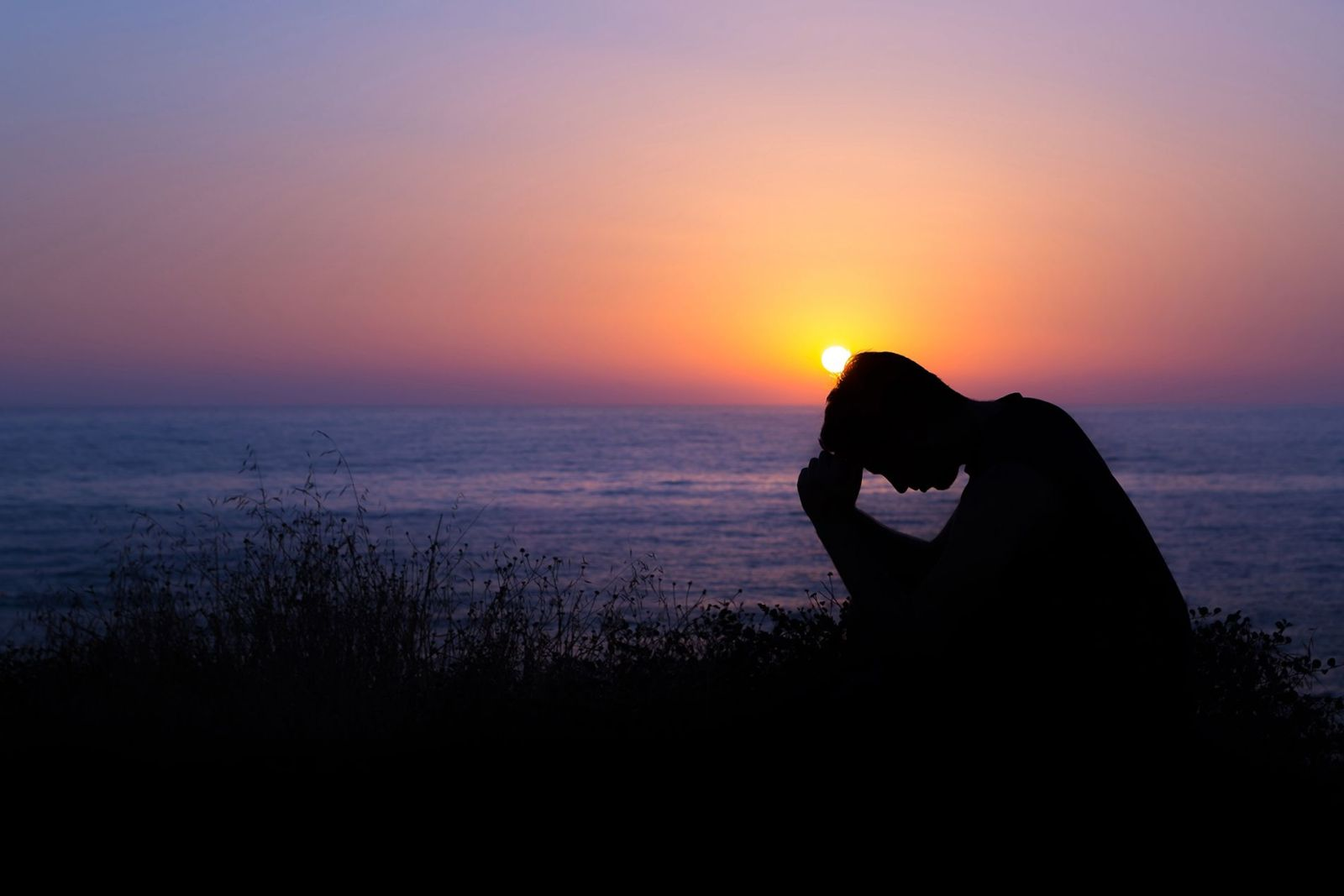 Man prays at sunset