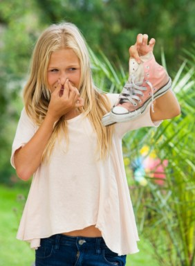 Austria, Teenage girl holding sneakers