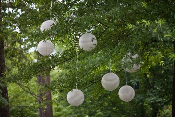 Hanging white lanterns in trees wedding ceremony Japanese Garden