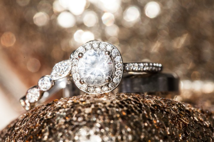 close up of round wedding ring on a glittery surface