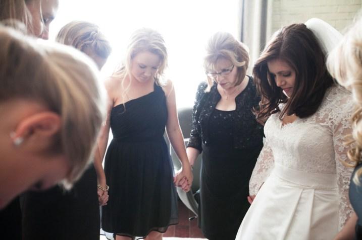 bride, bridesmaids, and mom praying before the wedding