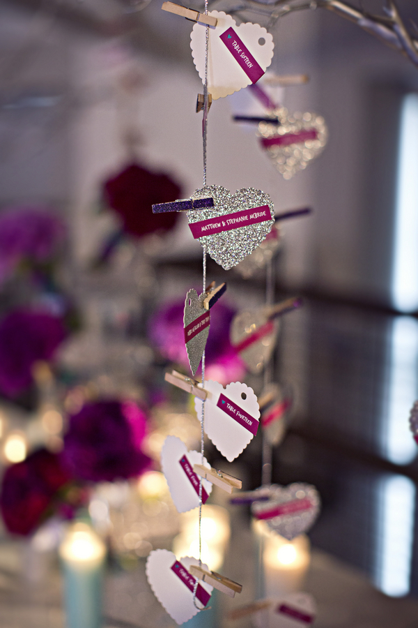 silver glitter heart escort cards hanging on silver tree with purple glitter clothespins