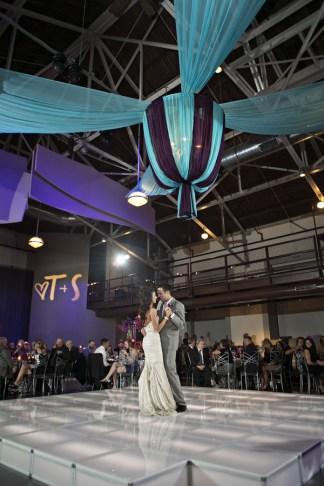 Bride and groom first dance acrylic glow dance floor with wedding monogram gobo and custom purple blue fabric chandelier