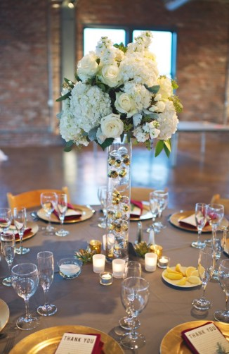Tall white hydrangea and rose centerpieces on vase filled with lightbulbs brick wall