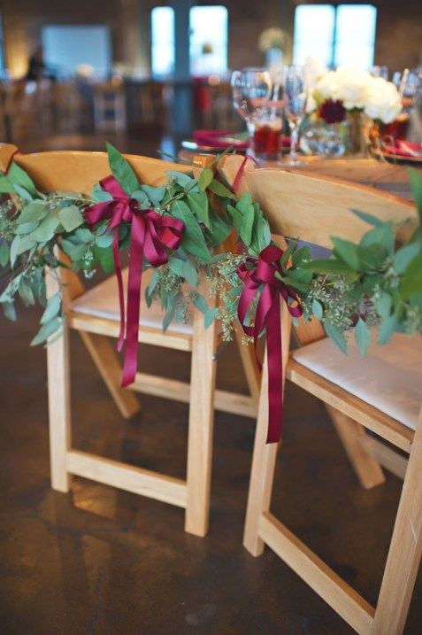 Greenery sweetheart table chairs with burgundy ribbons