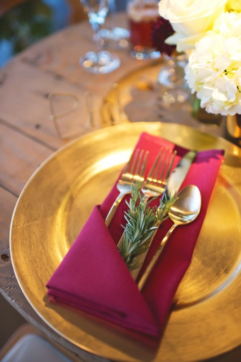 Gold flatware inside burgundy napkin with rosemary and gold charger and custom wired name