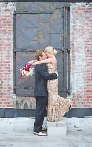 Groom and bride in gold sequin wedding dress in front of vintage metal door