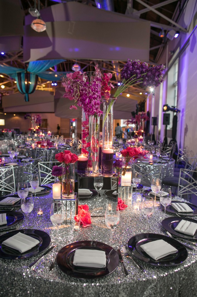 Towering centerpieces purple pink on silver sequin linen tablecloth orchids tall flowers full