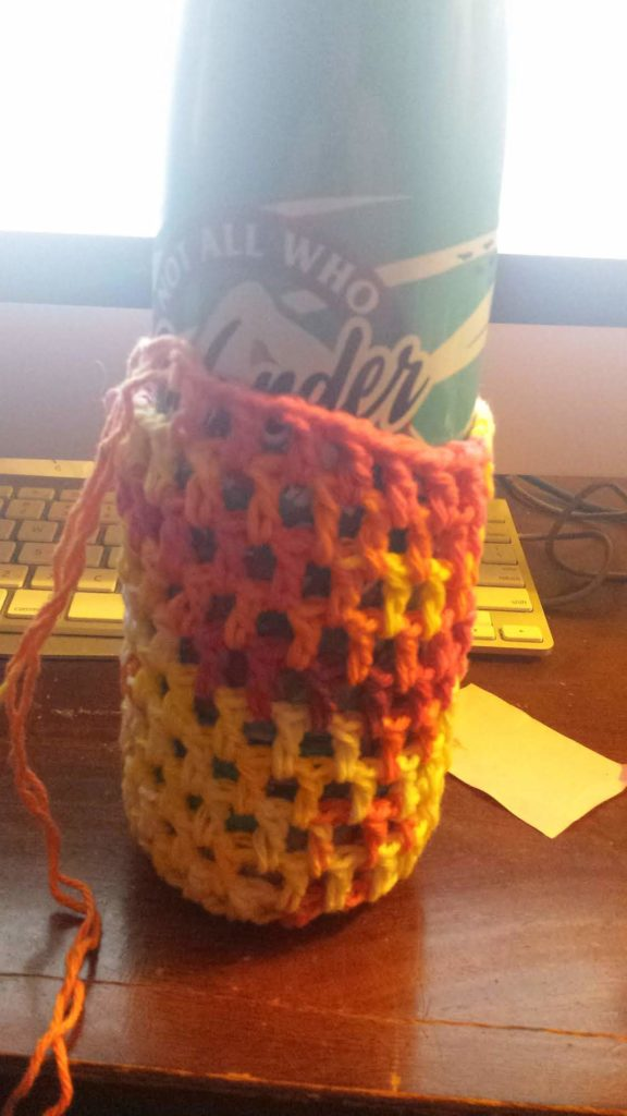 A picture of a water bottle with a half-finished water bottle holder on it, crocheted out of cotton yarn.