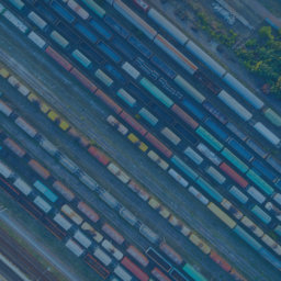 Top view of colorful cargo trains. Aerial view from flying drone of colorful freight trains on the railway station. Wagons with goods on railroad. Heavy industry. Industrial conceptual scene