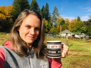 "Annie Tuttle holding a coffee cup with the text ""No. 1 Dad"" outside with house in background."