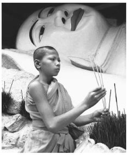 A young Cambodian monk burning incense. Monkhood offers a means to education for boys in Cambodia.