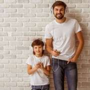 A dad and his child standing in front on f a white brick wall each with headphones listening to music and big smiles on their faces