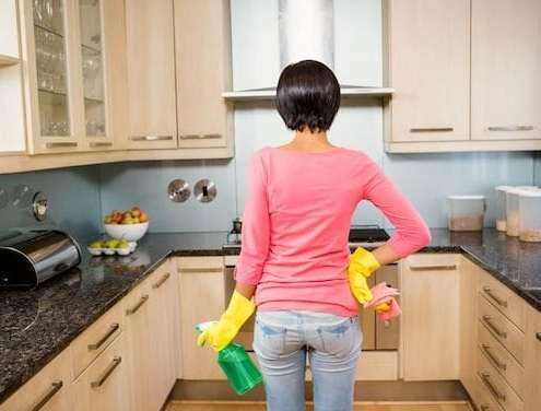 woman-cleaning-supplies-clean-gunk-grime-kitchen cabinets