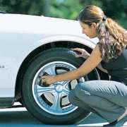 woman-in-business-attire-checking-proper-tire-pressure-to get-better-gas-mileage