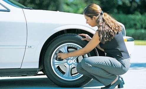 woman-in-business-attire-checking-proper-tire-pressure-to get-better-gas-mileage